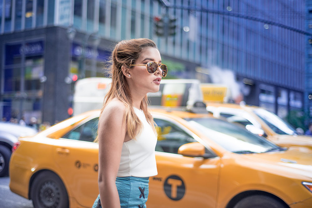 New York Travel Photos in Manhattan of a girl waiting for a yellow cab taxi