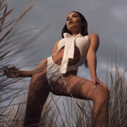 Girl wearing a white body suit and a bow posing in sand dunes surrounded by pampa grass