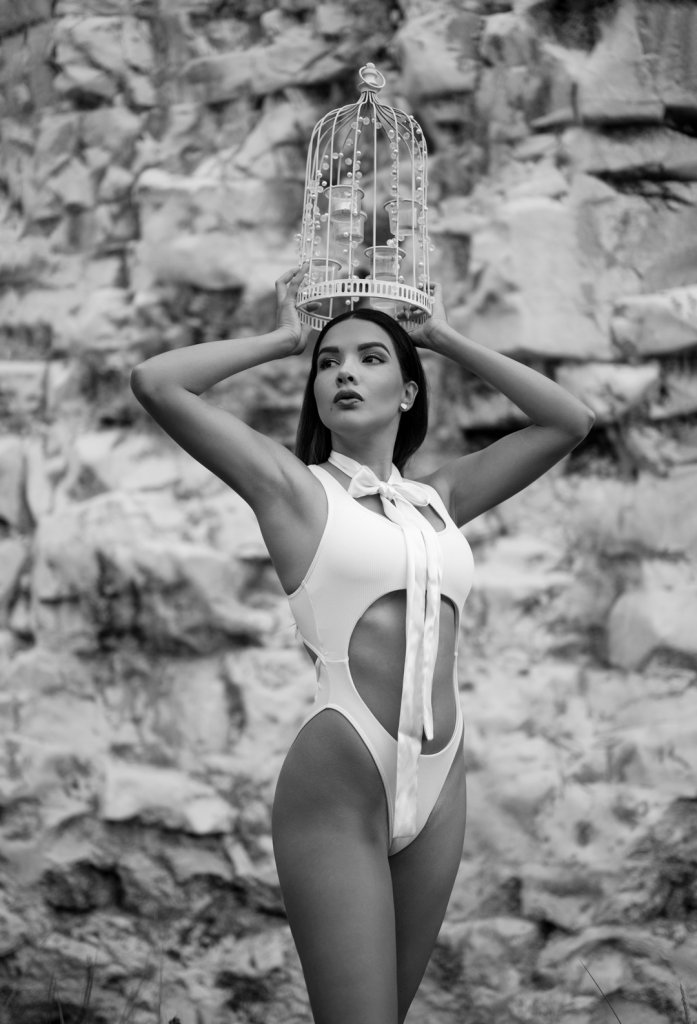 Girl wearing a white body suit and a bow posing at the beach with a cage on her head