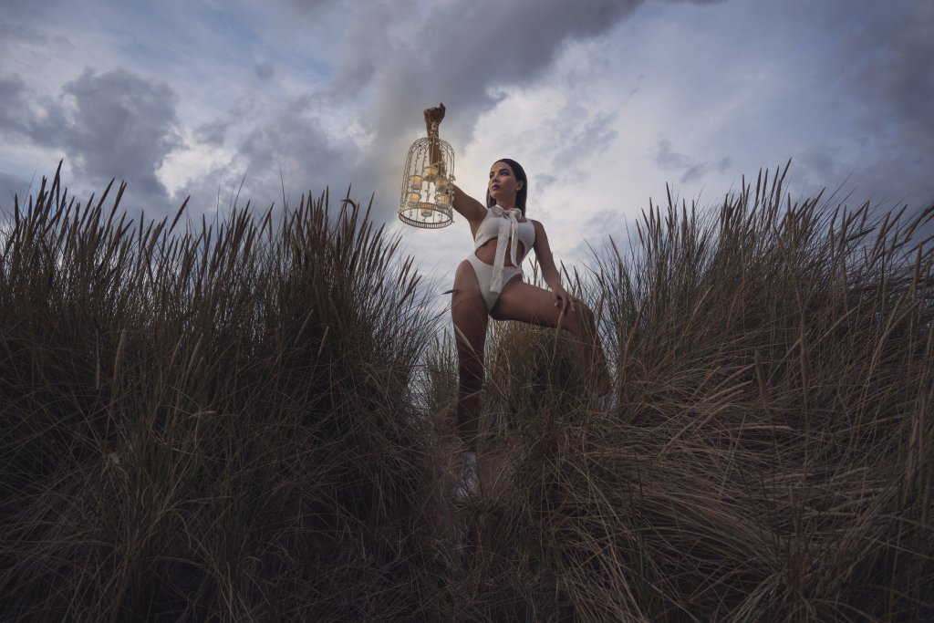 Girl wearing a white body suit and a bow posing in sand dunes surrounded by pampa grass while holding candles in a cage