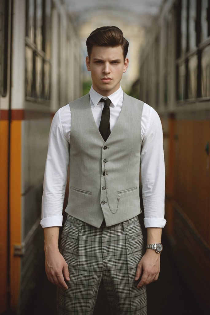 Male fashion model wearing a grey suit while standing in the middle of two yellow trains