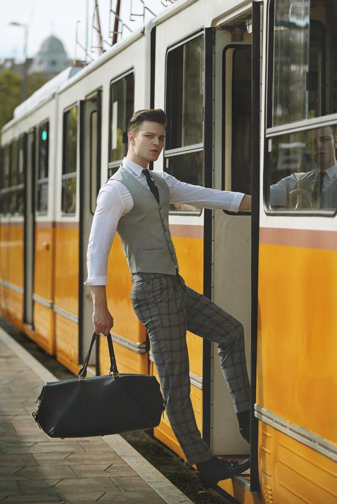 Male model wearing a grey suit taking the train