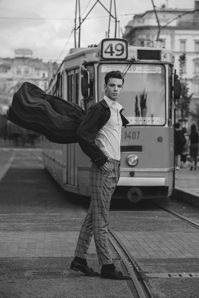 Male model wearing a black coat flowing in the air and a train in the background