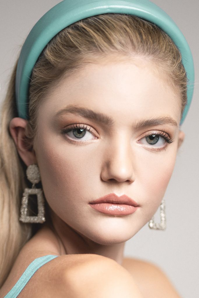 Portrait of blonde model during a studio photoshoot wearing a headband and big earrings
