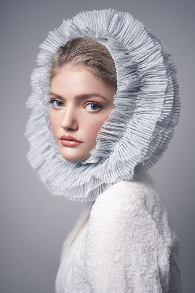 Portrait of blonde model during a studio photoshoot wearing a white blazer and headpiece
