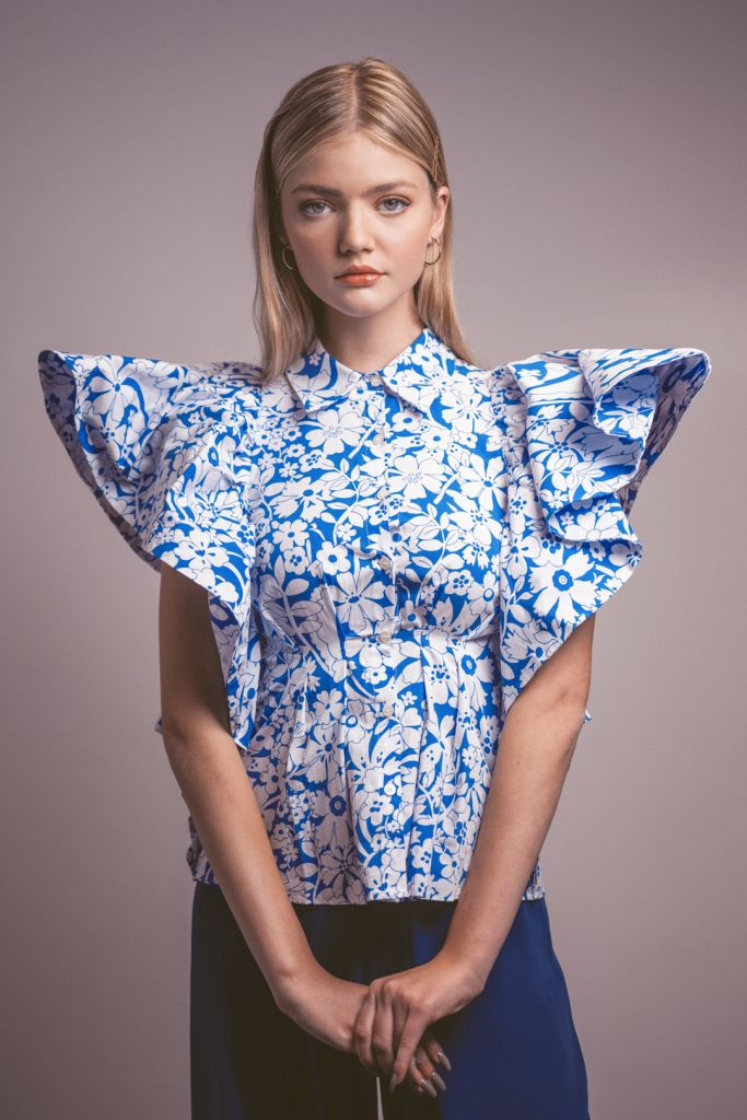 Blonde model during a studio photoshoot wearing a voluminous blouse with blue and white pattern