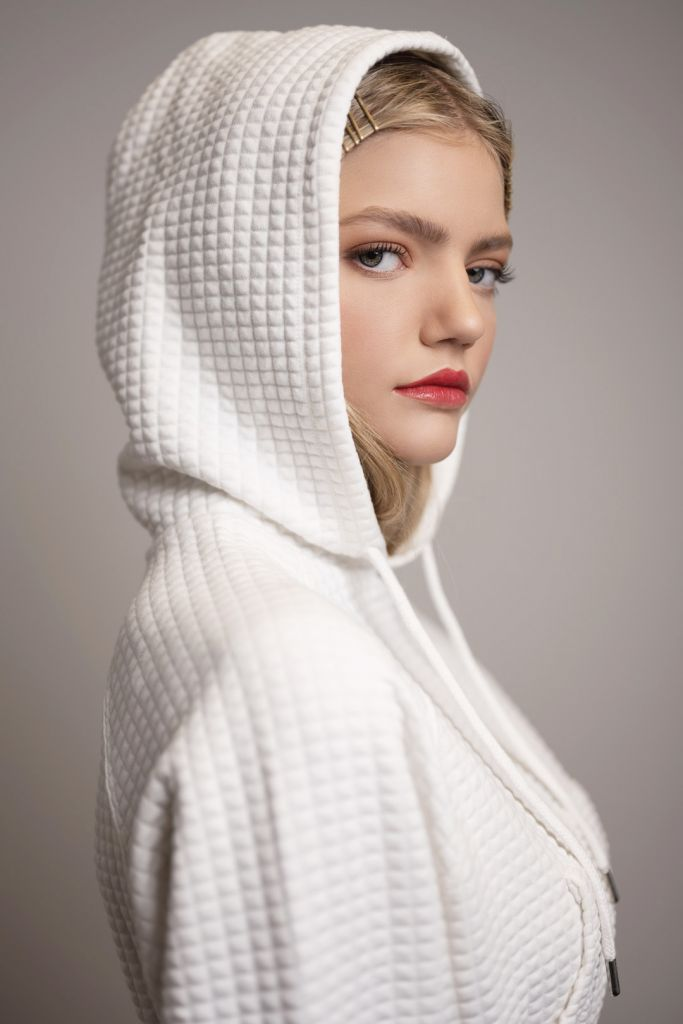 Portrait of blonde model during a studio photoshoot wearing a white hoodie