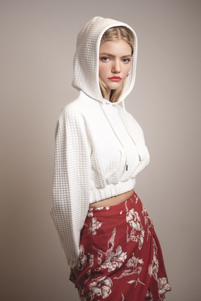 Portrait of blonde model during a studio photoshoot wearing a white hoodie and red skirt
