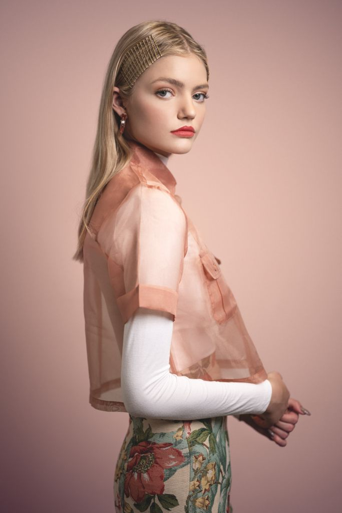 Portrait of blonde model during a studio photoshoot wearing a white turtle neck shirt and a sheer blouse