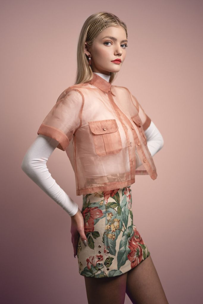 Portrait of blonde model during a studio photoshoot wearing a white turtle neck shirt, a sheer blouse and a floral mini skirt