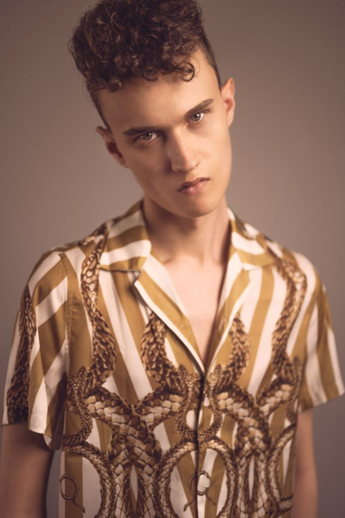 Close up portrait of male model with curly hair wearing golden shirt