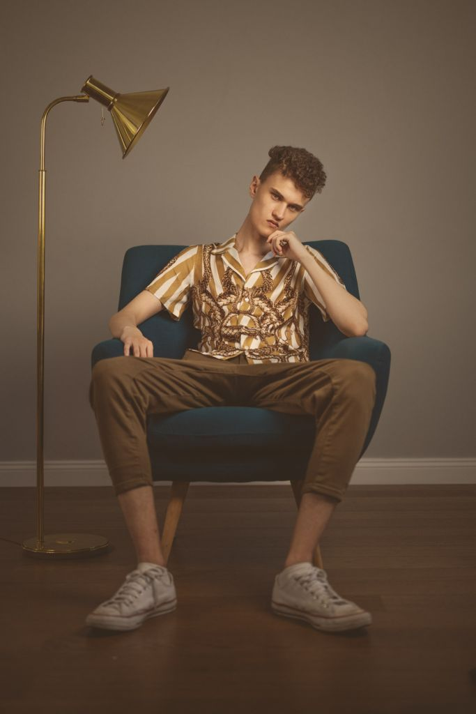 Male model with curly hair test shoot studio photography wearing a golden shirt and brown pants sitting on a sofa