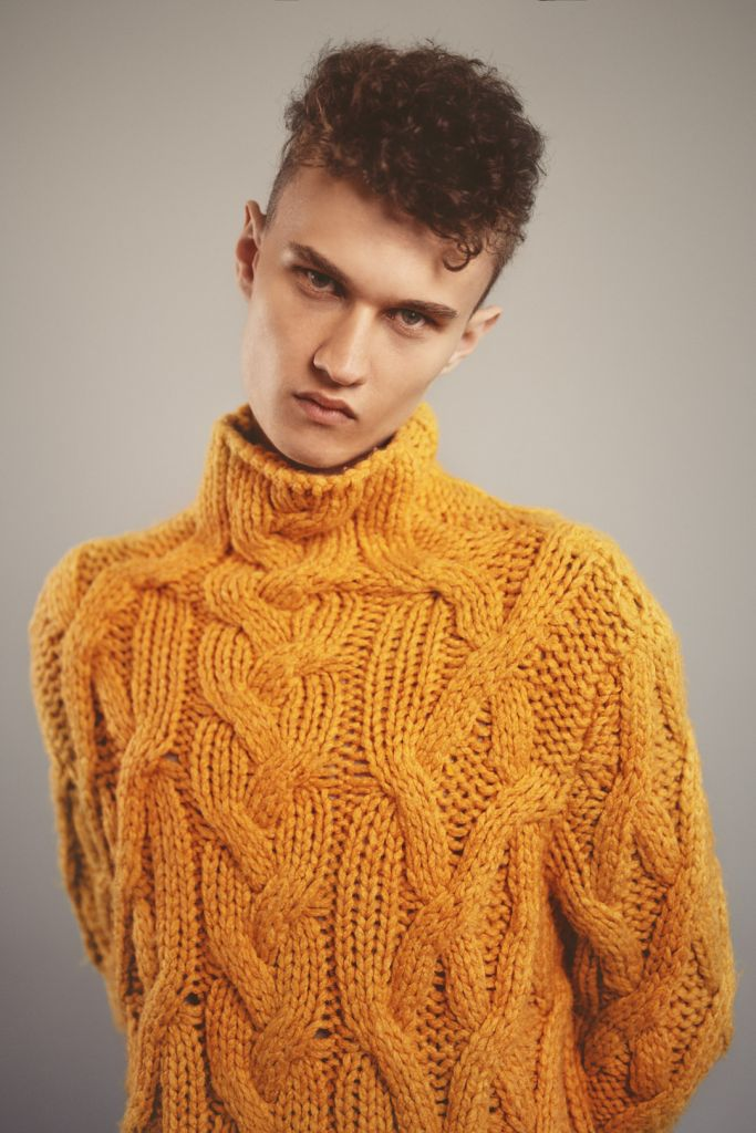 Close up portrait of male model with curly hair wearing a yellow cable knit sweater