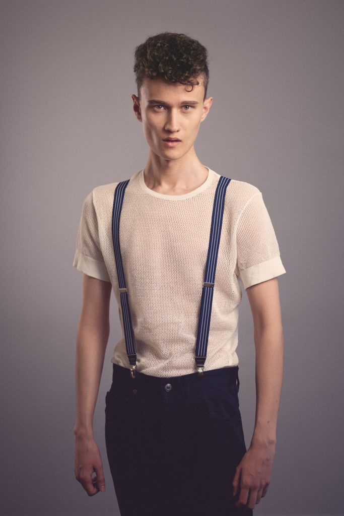 Male model with curly hair test shoot studio photography wearing white tshirt and suspenders