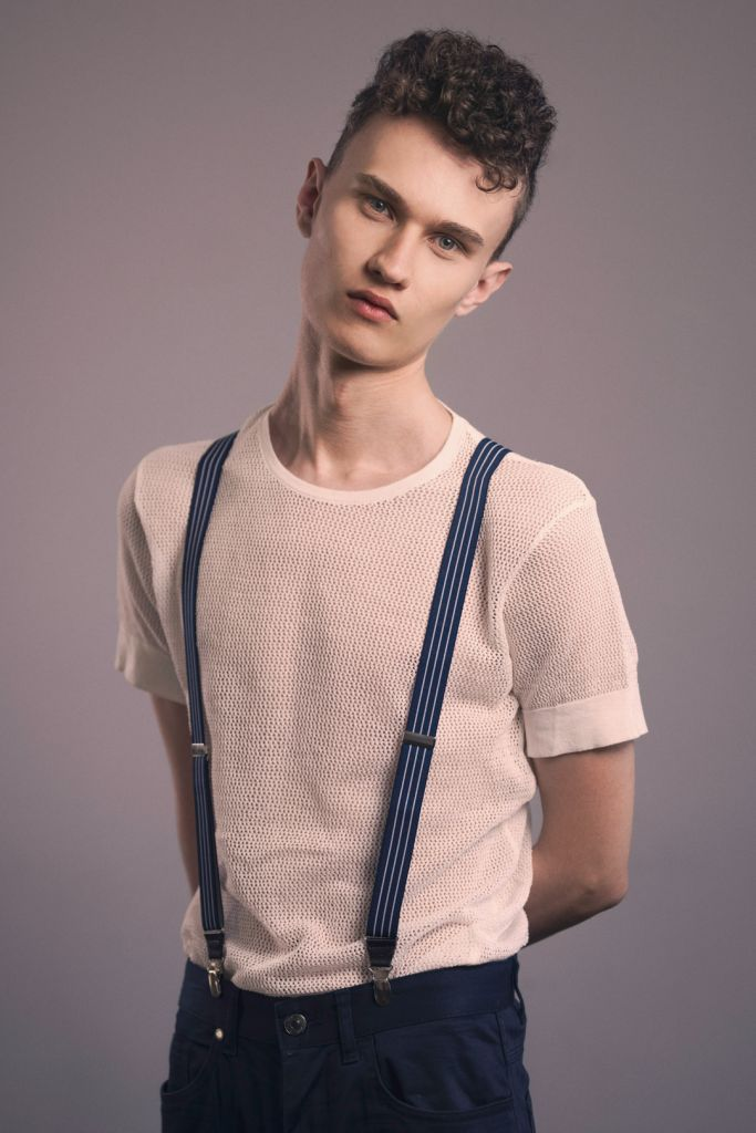 Male model with curly hair test shoot studio photography wearing white t-shirt and suspenders