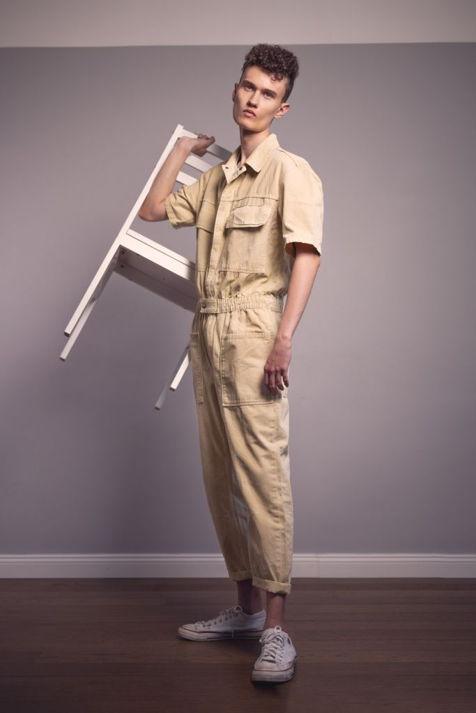 Male model with curly hair test shoot studio photography wearing a beige jumpsuit and holding a white chair