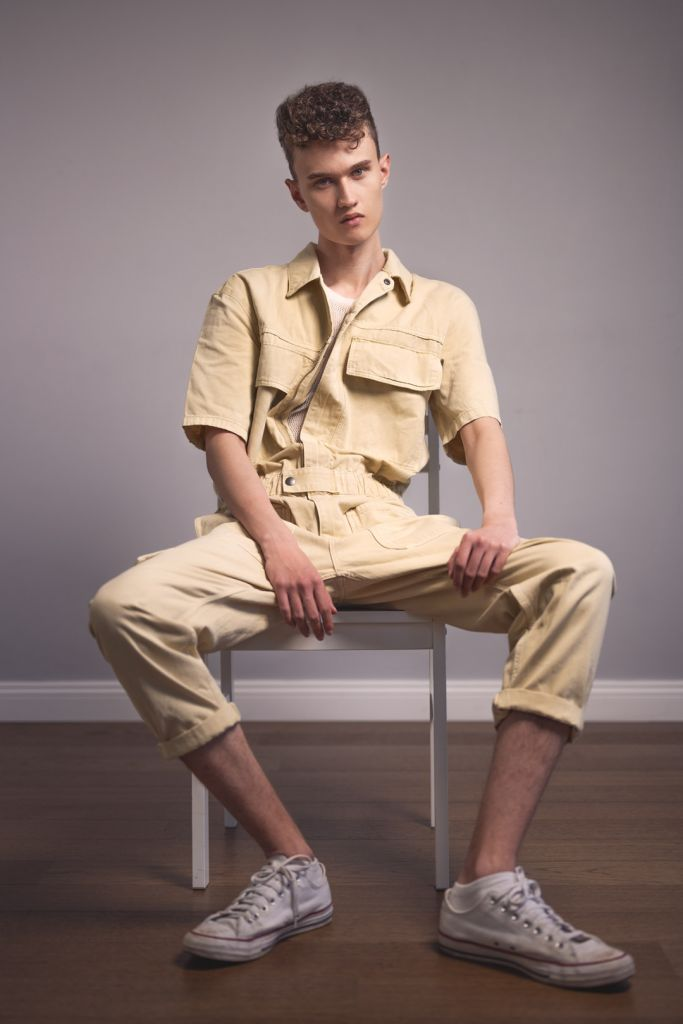 Male model with curly hair test shoot studio photography wearing a beige jumpsuit sitting on a chair