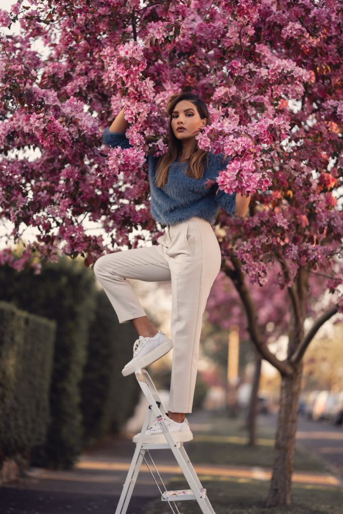 Model on a ladder with a pink cherry blossom tree