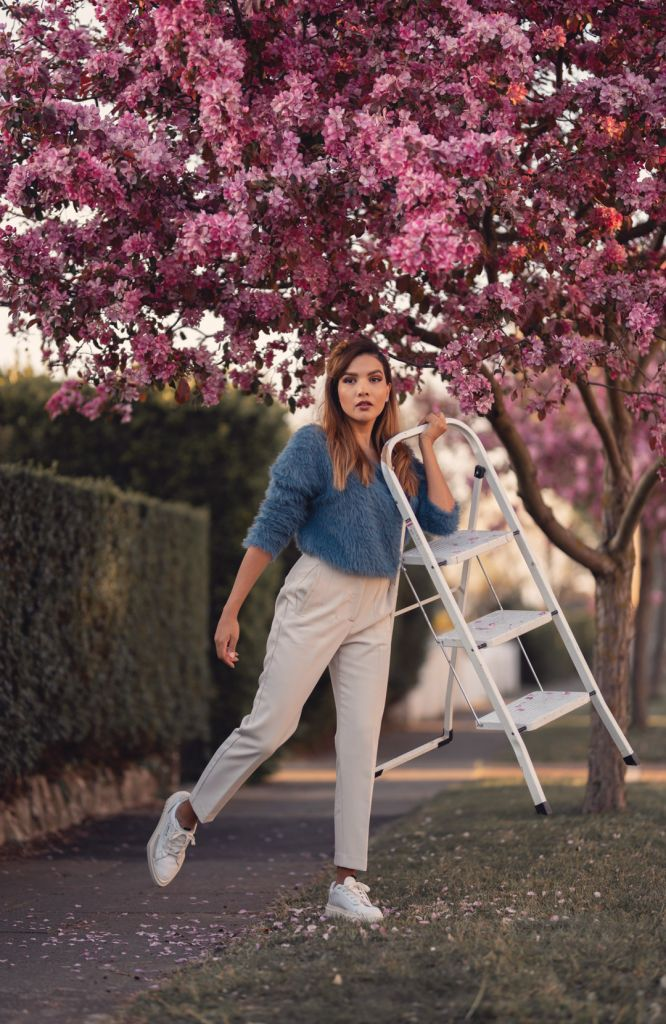 Girl holding a ladder under a pink cherry blossom tree