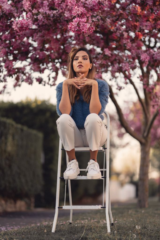Girl sitting on a ladder under a pink cherry blossom tree during the spring