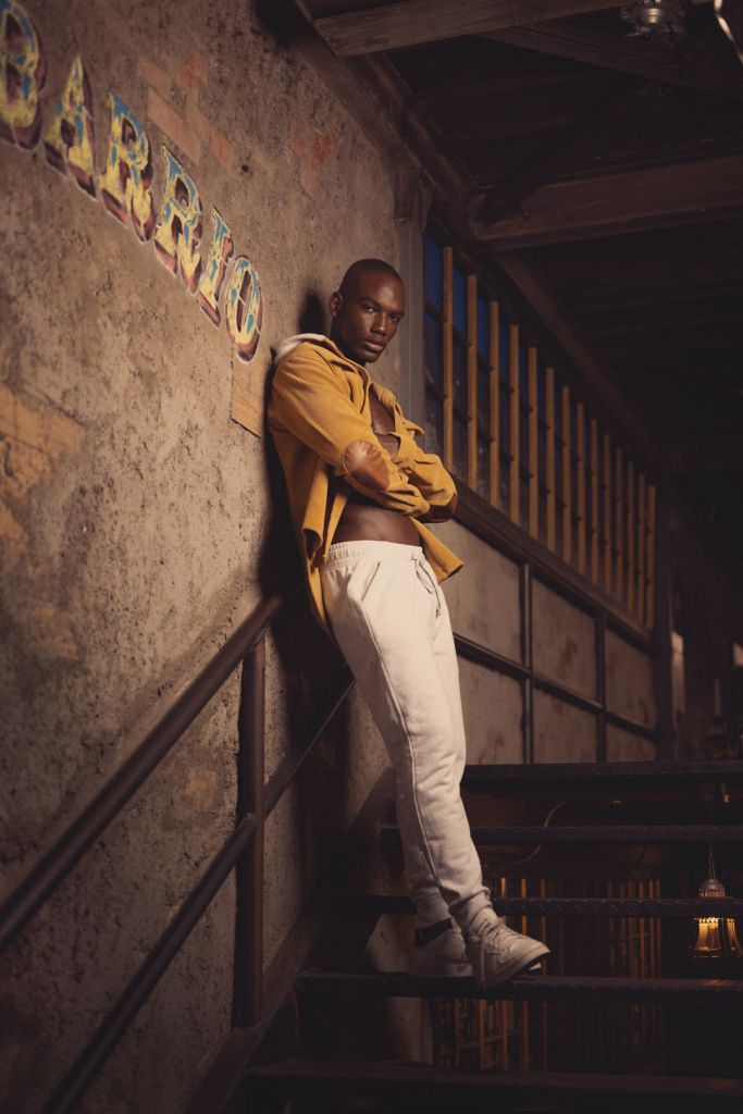 full length photography of black man wearing a mustard jacket, sweat pants, white sneakers standing on the stairs