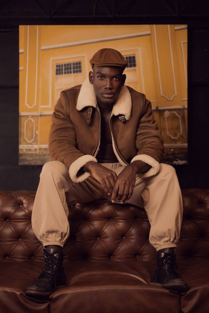 Black male model posing in a living room sitting on a sofa wearing a leather brown jacket, beige pants, combat boots, peaky blinders hat and leather bag