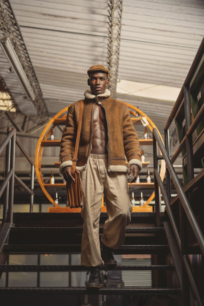 Black male model posing on stairs wearing a leather brown jacket, beige pants, combat boots, peaky blinders hat and leather bag