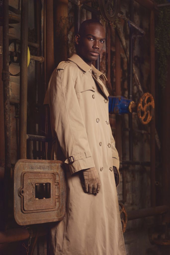 fashion editorial of a black male model wearing a camel trench coat and gloves