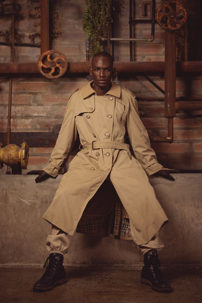 black male model wearing camel trench coat and boots in industrial location