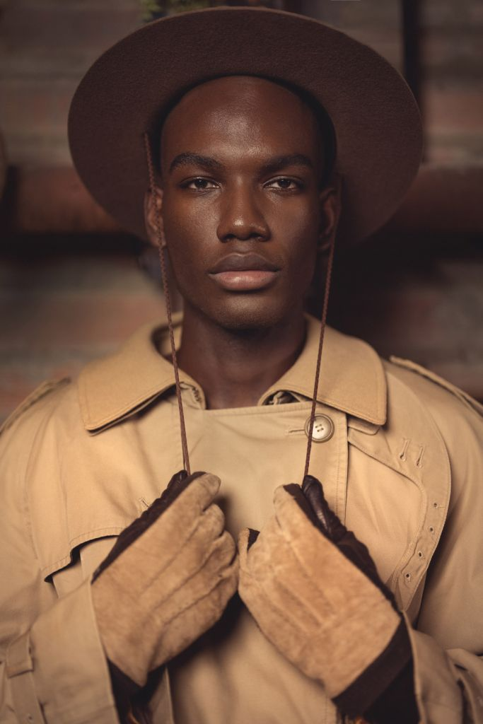 black male model portrait, men's fashion, trench coat, brown leather gloves and brown hat