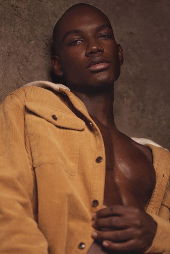close up portrait photo of black man wearing a mustard jacket
