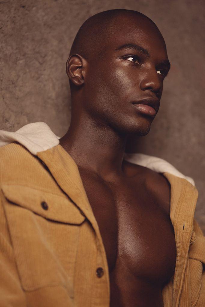 portrait photography of black man wearing a mustard jacket