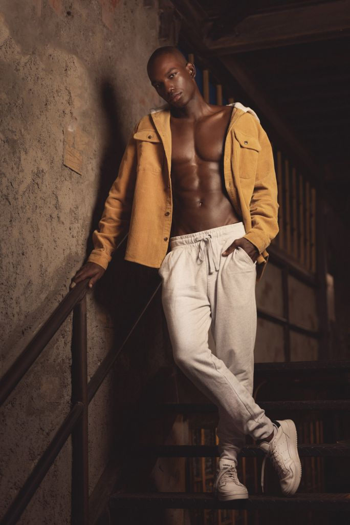black male model posing on stair, mens fashion casual style with sweat pants, mustard hoodie, white sneakers and showing abs