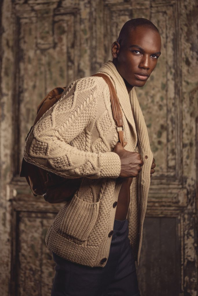 black male model photography portrait wearing knit sweater and leather backpack