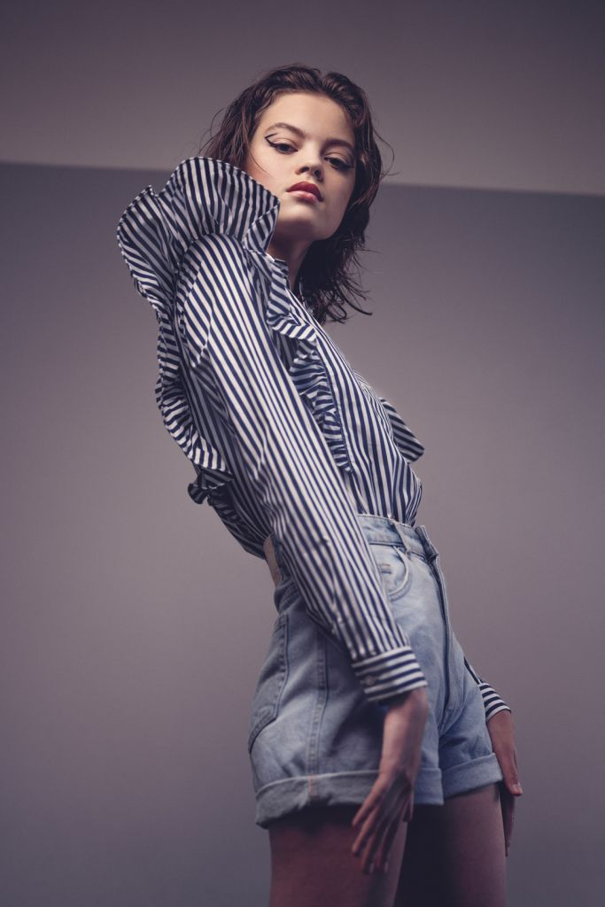 Model posing in the studio wearing shirt with stripes, big sleeves and denim shorts