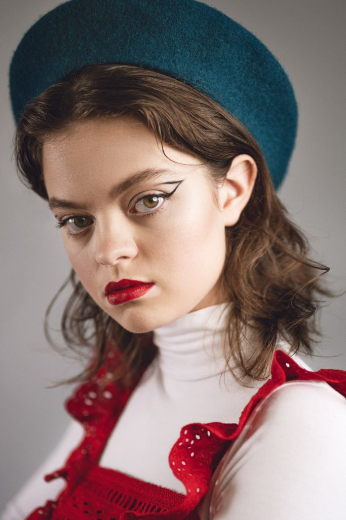 Portrait photography of model with vitiligo, short hair, with graphic eye makeup, red lips, white and red top