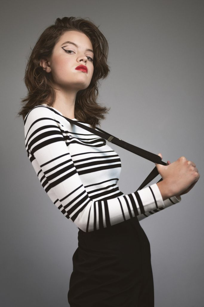Female model with short hair, graphic eye makeup, red lip stick. Wearing black and white top with stripes, suspenders and black pants