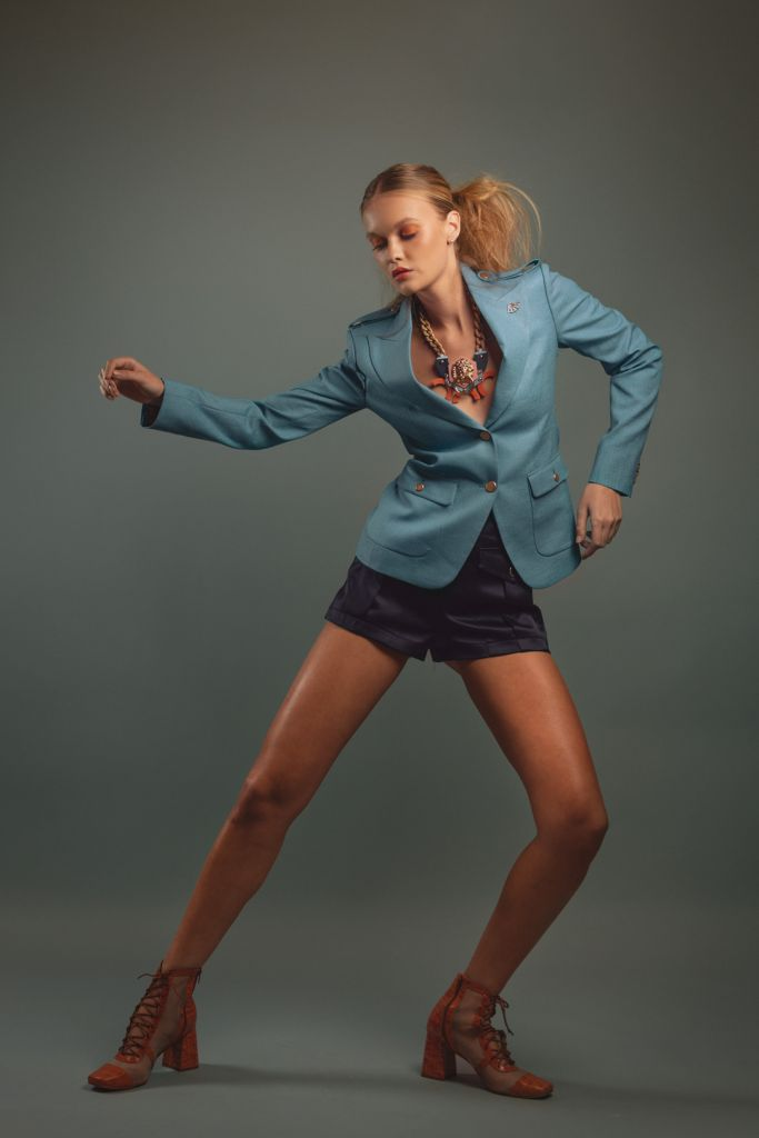 Model wearing a blazer, shorts and statement jewelry posing as a dancer