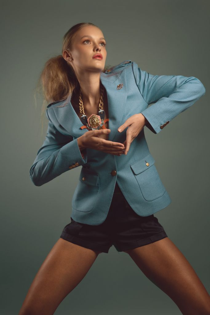 Model wearing a blazer, shorts and statement jewelry posing in the studio