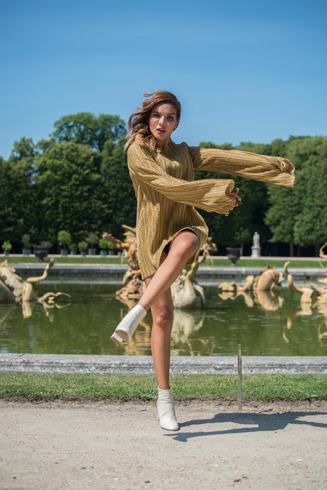Model jump posed wearing a golden dress and white shoes in a green garden