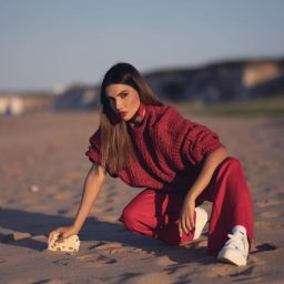 Model posing at the beach kneeling down on the sand wearing a red monochrome outfit
