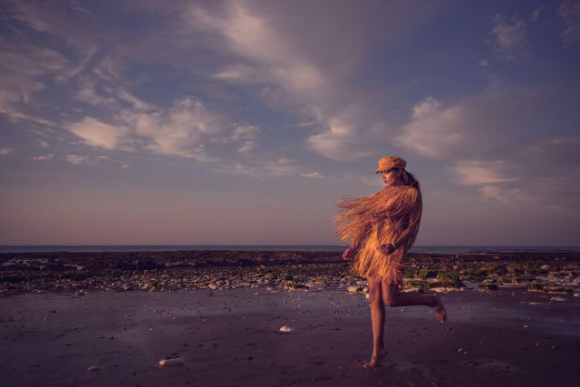 Portrait of woman wearing a yellow dress with fringeFashion Editorial on the beach front of Margate