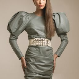 Portrait of model posing during a studio photography shoot wearing a mint leather dress